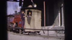 1962: men hanging off the steam engine of a train as it passes by BANGKOK, Stock Footage