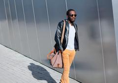 Fashion african man walks in evening city over urban background Stock Photos