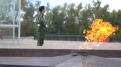 Memorial fire and armed guard wearing camouflage. Super slow motion long shot Stock Footage