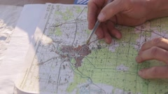 Hand with a pen on the map showing destination Stock Footage