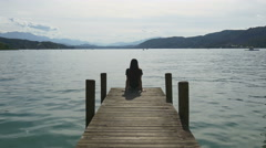 Relaxation at mountain lake. Woman sits on dock Stock Footage