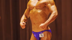 Bodybuilder demonstrating strong hands, torso and pectoral muscles at contest Stock Footage