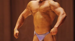 Athlete with ripped muscles and strong body standing on stage, bodybuilding Stock Footage