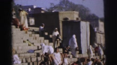 1962: people are seen bathing in some ritual or so and a boat seem passing by Stock Footage