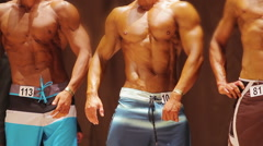 Sexy men with ripped muscles posing on stage at bodybuilding contest, sports Stock Footage