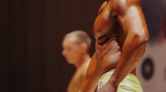 Athlete showing ripped torso muscles at professional bodybuilding contest Stock Footage