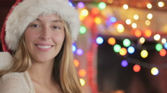 Close up portrait of a woman wearing a Santa hat in front of a fireplace Stock Footage