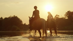CLOSE UP: Two girls horseback riding horses along the river at magical sunset Stock Footage