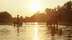 CLOSE UP: Two girls horseback riding across the river at magical sunset Stock Footage