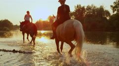 CLOSE UP: Two girls horseback riding brown and palomino horse in river at sunset Stock Footage