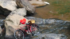 Red heart in toy bicycle on water background, Stock Footage