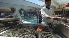 Two Cooks Cook Fresh Salmon On A BBQ Grill During An Alaskan Cruise Stock Footage