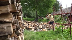 Man split wood with axe in one after other wooden log yard. 4K Stock Footage
