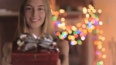 An attractive young woman wearing a Santa hat gives a wrapped gift at night Stock Footage