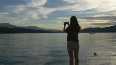 Woman photographing lake and ducks Stock Footage