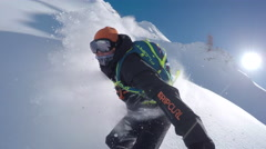 SELFIE: Extreme freeride snowboarder doing powder turns off-piste in mountains Stock Footage