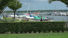 Woman walks by the Bellport marina Stock Footage