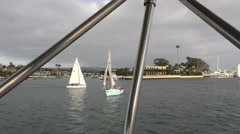 Sailboats waiting for race as seen from bimini top in the foreground harbor  Stock Footage