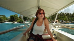 Young woman sitting under roof in small white outrigger boat, sailing Stock Footage