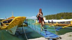 Young woman coming down on big yellow outrigger motor boat ladder to shore Stock Footage