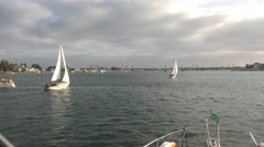 Sail boat in harbor on cloudy afternoon tracking shot as it tacks.mp4 Stock Footage