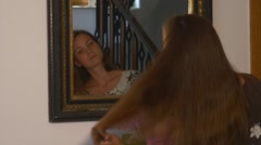 Woman brushing long hair in front of the mirror Stock Footage
