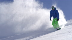 SLOW MOTION: Pro snowboarder riding fresh snow and doing powder turns off piste Stock Footage