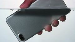 Male hand pulling waterproof new smartphone out of the water in slow motion Stock Footage