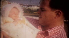 Proud father smiles as he holds his newborn baby - 3595 vintage film home movie Stock Footage