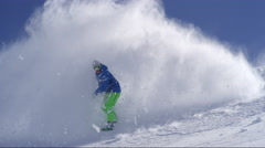 SLOW MOTION: Extreme snowboarder snowboarding in fresh powder snow on a mountain Stock Footage