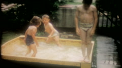 Children play in the new backyard pool - 3599 vintage film home movie Stock Footage