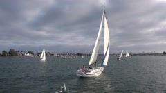 Sailing yacht moving away from race committee boat in harbor on cloudy aftern Stock Footage