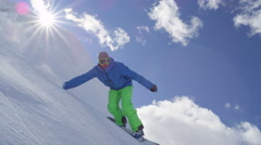 SLOW MOTION: Snowboarder riding powder snow and doing hand drag in sunny winter Stock Footage