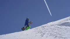 SLOW MOTION: Extreme freeride snowboarder hiking uphill on snowy mountain slope Stock Footage