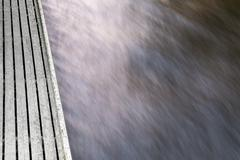 Abstract long exposure shot of water flowing in a river by a wooden dock Stock Photos