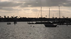 View of sun setting on a cloudy afternoon in harbor pans back and forth as th Stock Footage