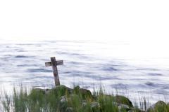 Wooden cross on the shore Stock Photos