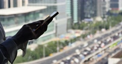 4k,woman using a smartphone with business building & urban traffic background. Stock Footage