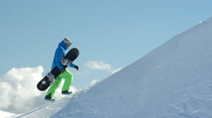 SLOW MOTION: Extreme freeride snowboarder hiking uphill towards mountain summit Stock Footage