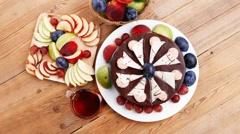 Whole big chocolate cream brownie cake with hot tea mug on wood Stock Footage