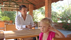 Conjurer Shows Card Pack Trick to Little Girl at Table Stock Footage
