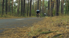 Two riders on ski-rollers ride woods Stock Footage