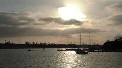 Perfectly serene shot of late afternoon sun behind clouds in harbor with yac Stock Footage