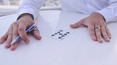 Closeup Conjurer Hand Marks Shades Card with Pen at White Table Stock Footage