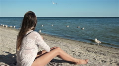 Woman feeding hungry seagulls bread on the seafront Stock Footage