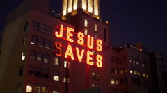 JESUS SAVES neon sign on building Stock Footage