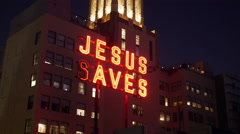 JESUS SAVES neon sign on building and Light Effects Stock Footage
