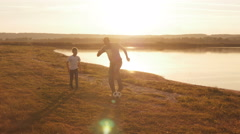 Young family frolicked together to play football football on the beach at sunset Stock Footage