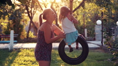 Mother twists the little daughter on a swing Stock Footage