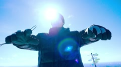 Young happy man snowboarder rises hands in Mountain sin slowmotion on the sun Stock Footage